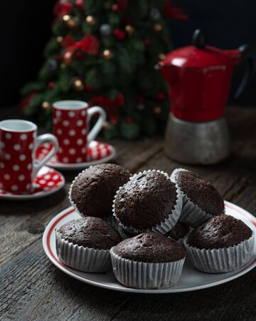Chocolate muffins on dark wooden background. Shallow depth of field.