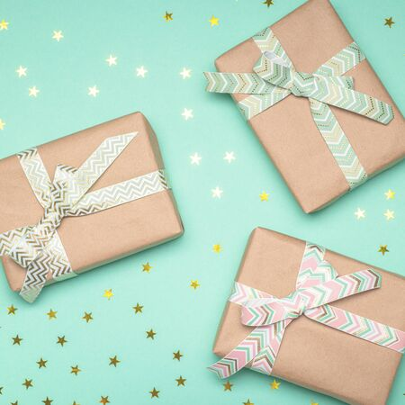 Gift boxes with ribbons on turquoise background. Holiday concept.