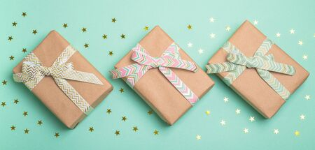 Gift boxes with ribbons on turquoise