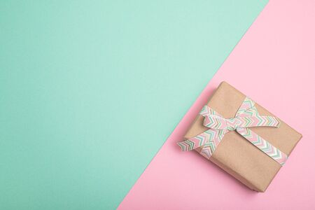 Gift box with ribbon on duo tone bright background with copy space Фото со стока