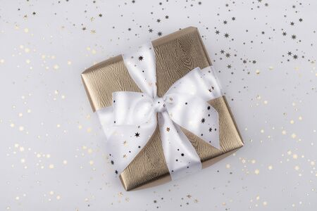 Gold gift box with a white ribbon.
