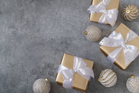 Christmas white balls and gift boxes on a grey background.