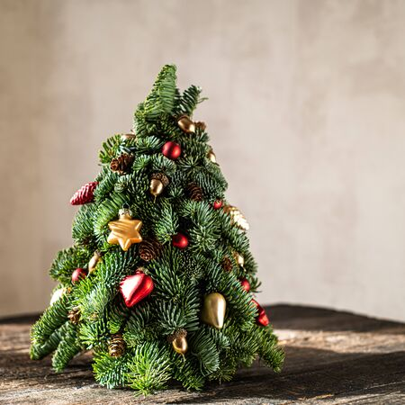 Christmas tree on a brown, wooden background. Фото со стока