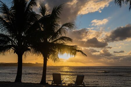 Romantic sunset with palm trees on the ocean with two sun loungers. Фото со стока