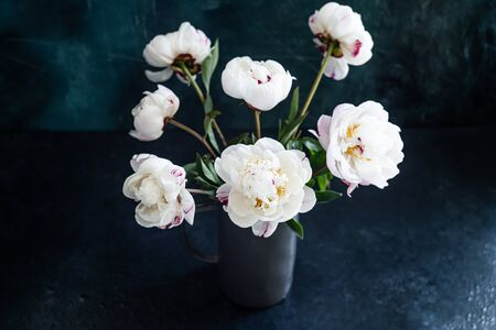 Bouquet of fresh white peonies in a gray vase on a dark background.