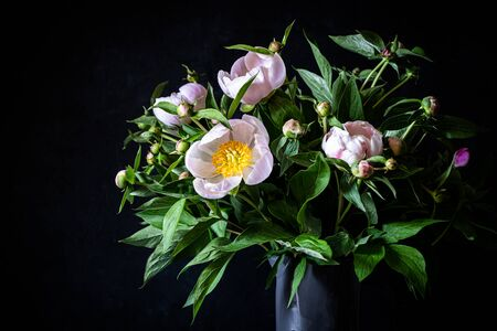 Bouquet of pink peonies in a grey vase on a dark background.