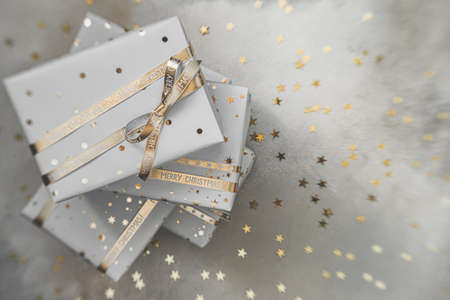 Gift boxes in white paper with stars and dots with golden ribbons on grey background. Flat lay with copy space.