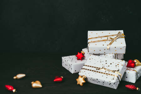 Gift boxes in white paper with stars and dots with golden ribbons on dark background.