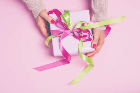 Pink gift box with bow in womans hands.