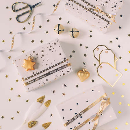 Gift boxes in white paper with stars and dots with golden ribbons on white background. Фото со стока