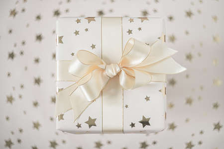 Gift box with beige bow on a light background with stars. Flat lay with soft focus. Фото со стока