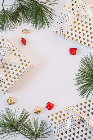 Gift boxes in white paper with golden hearts on white background. Фото со стока