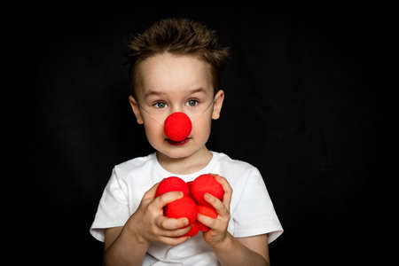 Boy with a clown red nose and red noses in hands. Red Nose Day.
