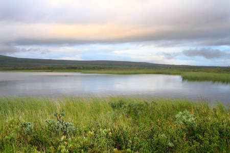 Lake in Lapland with vegetation, hills and clouds photo
