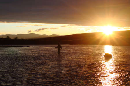 Fisherman fishing standing in the river with a fly rod. Amazing sunset in the mountains behind him Stock Photo - 8111637