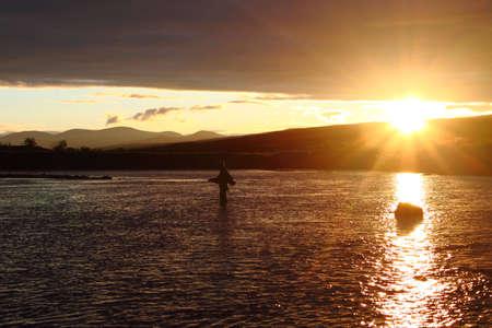 grayling: Pescador permanente de pesca en el r�o con una varilla de mosca. Impresionante puesta de sol en la monta�a detr�s de �l
