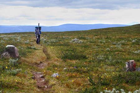 grayling: Mochileros con equipos de pescadores vagando en el altiplano a lo largo de una ruta marcada hacia las monta�as azules