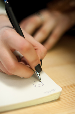 todo list: paper in business woman beautiful female hand writing notes on a table black manicure and blank letter