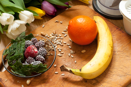 banana, orange,frozen strawberries blackberries and seeds vivid smoothie ingredients and blender, juicer, tulips on the background on wooden