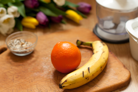 banana, orange and seeds vivid smoothie ingredients and blender, juicer, tulips on the background on wooden Stock Photo