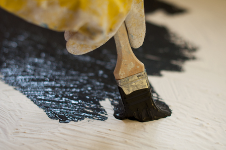housepainter: hand in yellow glove paints a black surface with white stone. Copy Space. Stock Photo