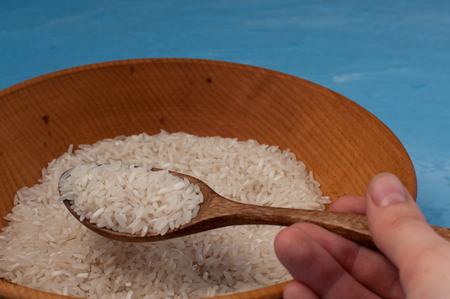 carbohydrates: Raw rice in wooden bowl with wooden spoon on blue background.