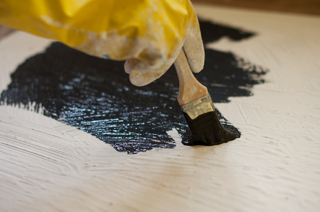 housepainter: hand in yellow glove paints a black surface with white stone.