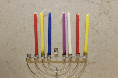 Colorful Chanukah candles lit in the menorah, Colorful Hanukkah candles are arranged in the Menorah according to the days of the holiday