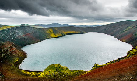 Red rock, green grass and turquoise waters of Lake Ljottipolur formed in the crater of a now extinct volcano