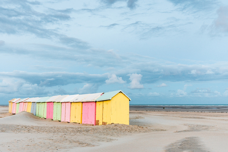 Multicolored bathing cabins lined up on the deserted beach of Berck-Plage in the early morning