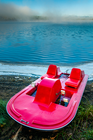 A pedal boat on the edge of a lake early in the morning in Saint-aime-des-Lacs in Quebec, province of Canada