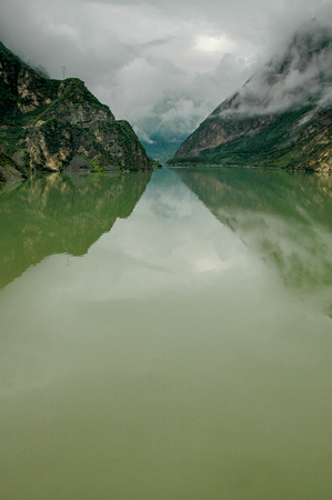 The cloudy sky is reflected in a lake in a mountainous region of Sichuan, China.