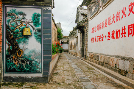 Wall mural and ideograms in an alley of the old city of Xizhou in Yunnan, China Editorial