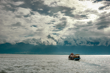 A boat advances on Lake Erhai towards the city of Dali while the clouds cling to the surrounding mountains