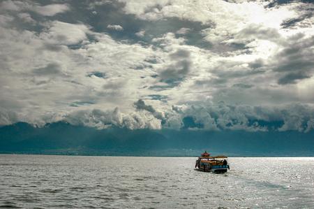 Ein Boot fährt auf dem Erhai-See in Richtung der Stadt Dali, während die Wolken an den umliegenden Bergen haften Standard-Bild