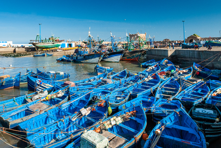 A fleet of blue fishing boats huddled together in the port of Essaouira in Morocco.