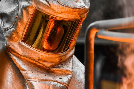 In a foundry workshop. The molten metal contained in a crucible is reflected on the visor of a worker's safety helmet