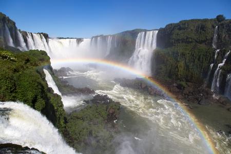 Amazing National Park of Iguazu Falls with a full rainbow over the water, Foz do Igua u, Brazil Stock Photo