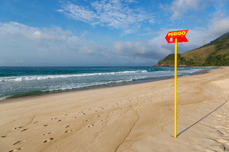 Marisa beach in Sao Paulo - small beach sign adverting to danger about the current rip in the sea. Brazil Stock Photo