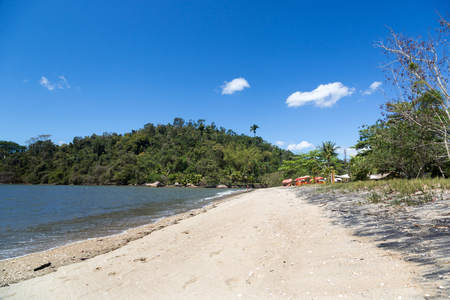 Paraty, Rio de Janeiro - Empty beach in a blue sky day, empty sand and a beach bar in the background in Paraty, Rio de Janeiro, Brazil