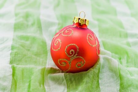 Red christmas-tree ball on green textile with grey stripes photo