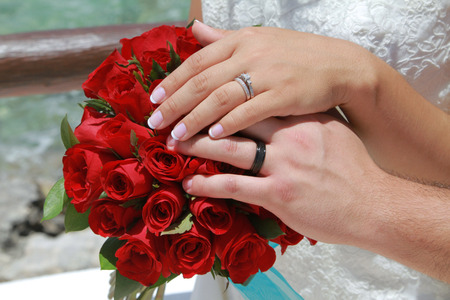 Bride and groom put their hands together on wedding bouquet, showing the rings photo