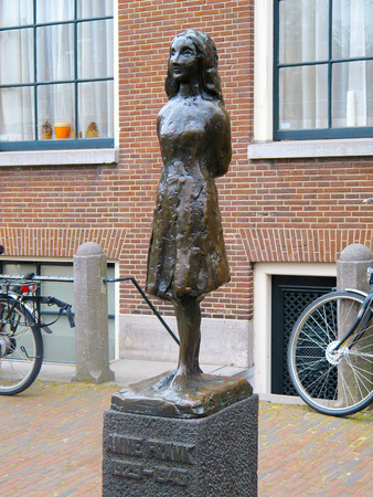 dutch girl: AMSTERDAM, NETHERLANDS-MARCH 13, 2011: Anne Frank statue in front of Anne Frank Museum in Amsterdam. A victim of Nazi Germany in World War 2 she wrote a diary of her short life before she was killed.