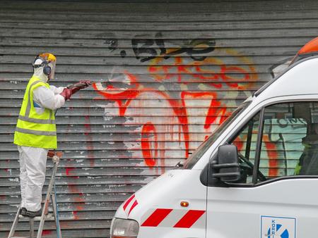 PARIS, Francja - październik 2012: Człowiek czyszczenia Graffiti rozpylany metalowe drzwi w Paryżu, we Francji.