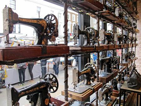 LONDON, ENGLAND - OKTOBER 2014: Schaufenster mit Nähmaschinen in einem Modegeschäft auf der Portobello Straße in London verziert.