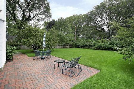 Brick patio with umbrella and chairs with large back yard photo