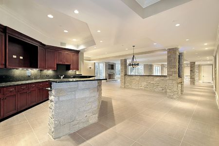 stone fireplace: Lower level stone  bar with kitchen and fireplace Stock Photo