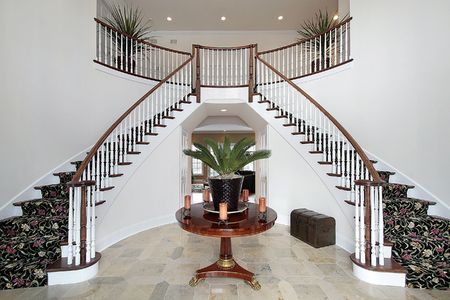 Modern foyer with double staircase and large circular table photo