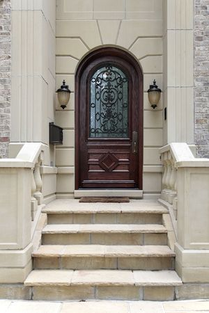Front door of luxury home with arch and stairs photo