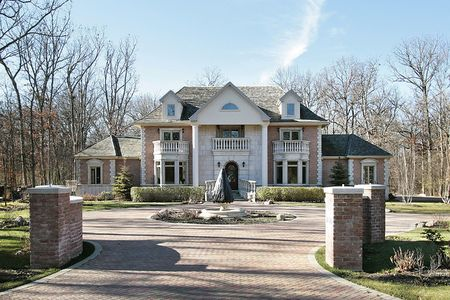 Large luxury home with shingle roof and brick drive photo